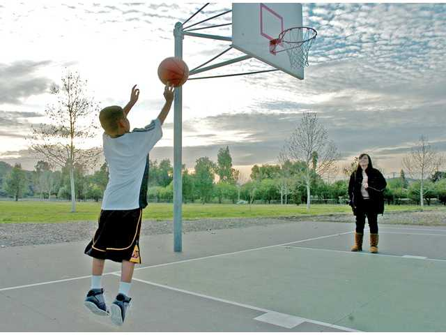 Nathan Perez, 8, plays basketball as his mother, Patricia, watches at Central Park in Saugus on Tuesday. Clouds roll through the skies over the Santa Clarita Valley in advance of another Pacific storm that is expected to bring more rain to the area.