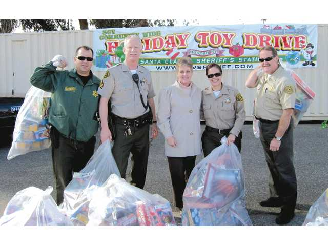 Sgt. Gregg Lewison, second from left, and the team behind Santa Clarita Sheriff's Communitywide Holiday Toy Drive present toys to Cheryl Jones, center, of the center. The toys were distributed for the holidays to families in need.