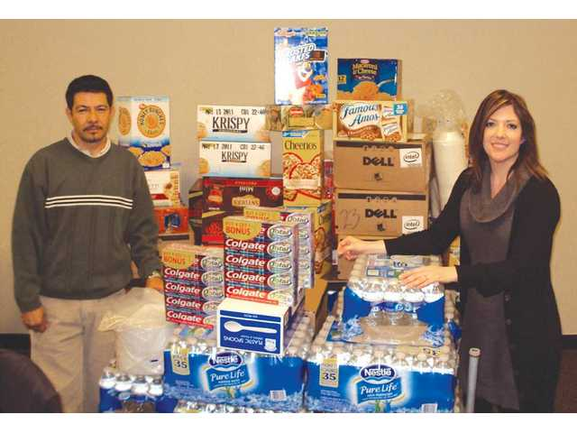 Members of Nexus Valencia staff pose with some of the donations raised by the company for the  Valley Food Bank. For the last five years, the  company has challenged its seven regional offices to donate packaged food items during the holidays.