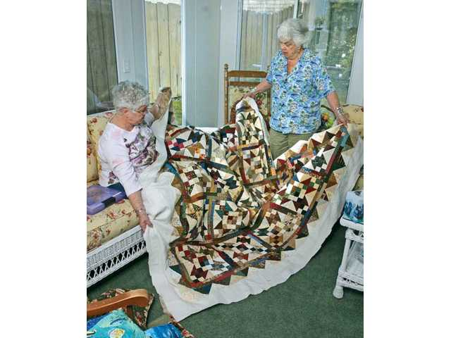 Pat Palmer, left, and Beverly Van Cleave, members of the Old Remnants quilting group, display a quilt made of pieces of scrap materials Dec. 16. The Saugus group has met  on the fourth Sunday of each month for more than a decade. On those days, up to 16 Old Remnants members get together for six hours of quilting, eating potluck dishes and talking.