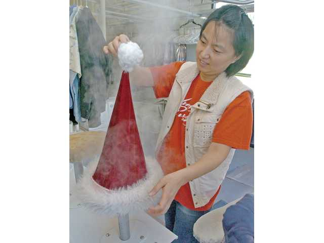 Leah Shim steam cleans a Santa hat at Grace Cleaners in Castaic on Thursday.