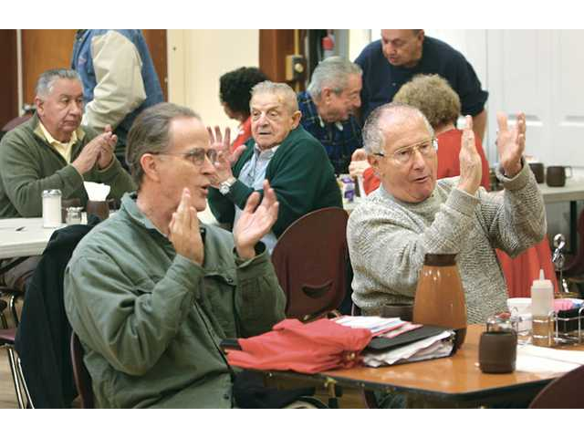 Ricardo Fernandez, left, and Richard McNally applaud the Golden Pen Writers at the SCV Senior Center on Dec. 21.