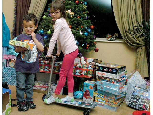 Luke Follett, 5, left, and his sister Samantha, 8, play with new toys provided by the community at the home of Mike Smith in Newhall on Wednesday. The Folletts' Newhall homewas burned in the early morning hours of Nov. 27 while the Folletts were visiting family. The cause is still under investigation.