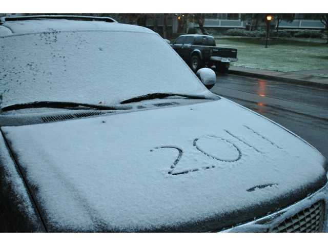 "A car on Claudette Place in Canyon Country sports a layer of snow and ""2011"" inscribed on its hood. The new year got off to a wintry start Sunday with the first snow in the Santa Clarita Valley since 2007."