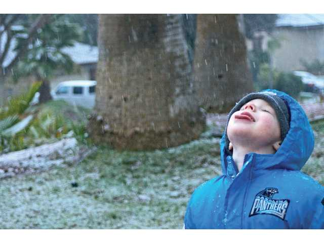 Alexander Hohler, 4, of Saugus, attempts to catch a snowflake with his tongue in the front yard of his Saugus home on Sunday.