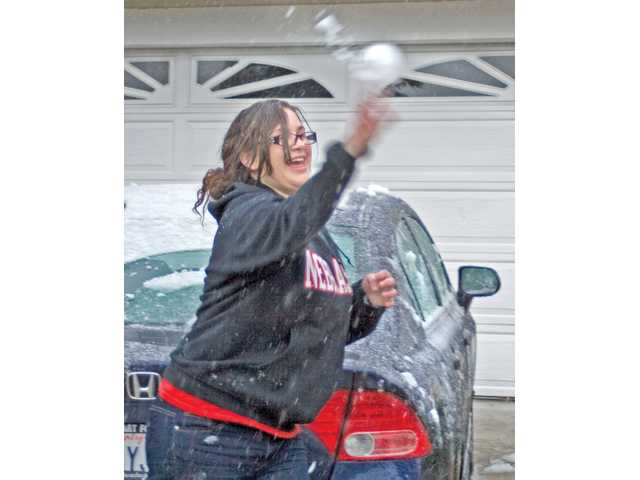Wendy Heirshberg, 20, flings a snowball during the light snowfall on Sunday at her home in Saugus.