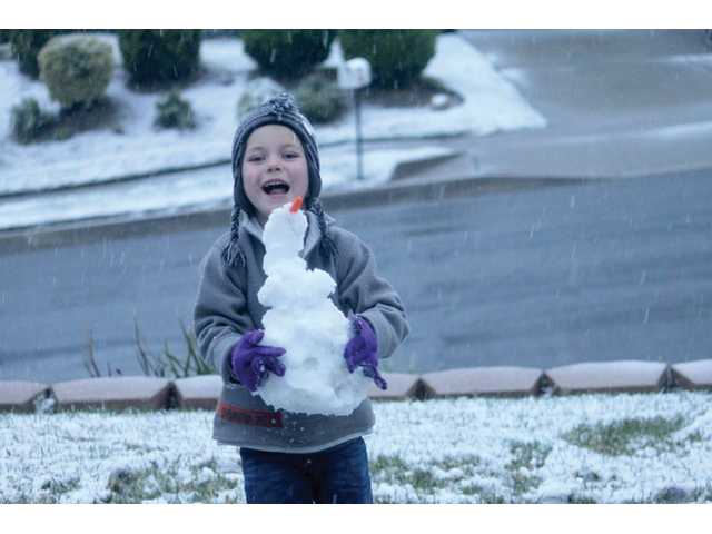 Ty Dawson, 5, holds his snowman while having fun in the rare Santa Clarita snow.