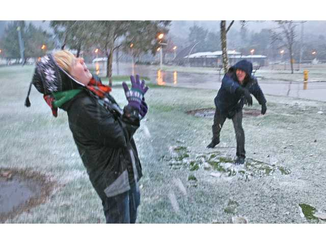 Randy Simer, right, of Saugus, throws a snowball at his son Cameron Simer, 12, at Central Park in Saugus on Sunday. Santa Clarita Valley residents had an opportunity to play in the snow as a surprise snowstorm cooled the area.