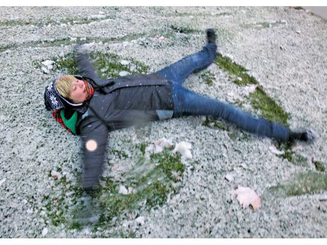 Cameron Simer, 12, of Saugus, make a snow angel at Central Park on Sunday after a light snowfall blanketed the SCV.