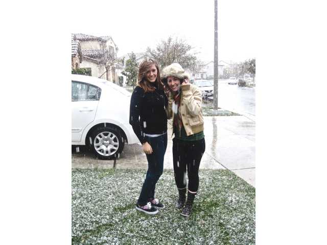 Arielle Griffith, 18, and Arika Griffith, 19, enjoy the snow in Valencia by Valencia High School.