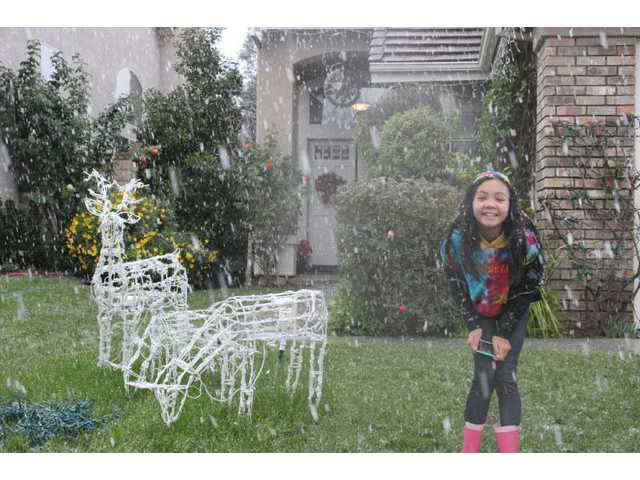 (Left) Rachel Suen, 12, enjoys the snow flurries at home in Valencia.