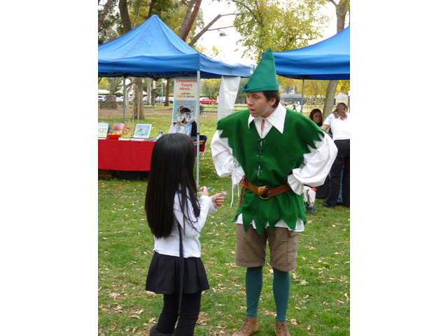 One of The Signal's Reporters for a Day talks to an actor at the Literacy & Arts Festival at Hart Park on Dec. 4.