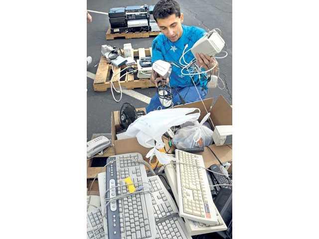 Canyon High School student Salem Hawatmeh, 17, separates a set of speakers from a box of computer components, phones and television remotes dropped off during an e-waste fundraiser in the school's parking lot Jan. 9, 2010.