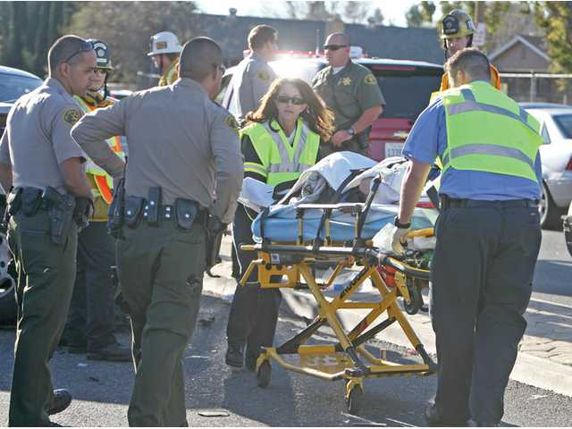 EMTs transport a patient on a stretcher to a waiting ambulance. Two ambulances were requested at the crash scene, but it was unclear Monday of the extent of injuries to any drivers or passengers.