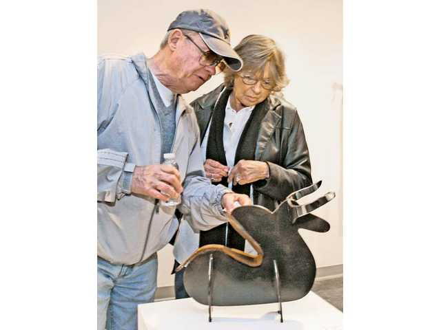 "Michael and Patricia Kurthy, of Canyon Country, look at a welded steelwork titled ""Variation"" by Dale Thayer at COC's Art Gallery."