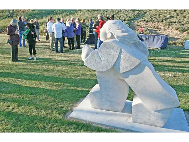 "A small group gathers at the unveiling ceremony Wednesday for  a sculpture titled ""Friends,"" by local artist Madeline Wiener."