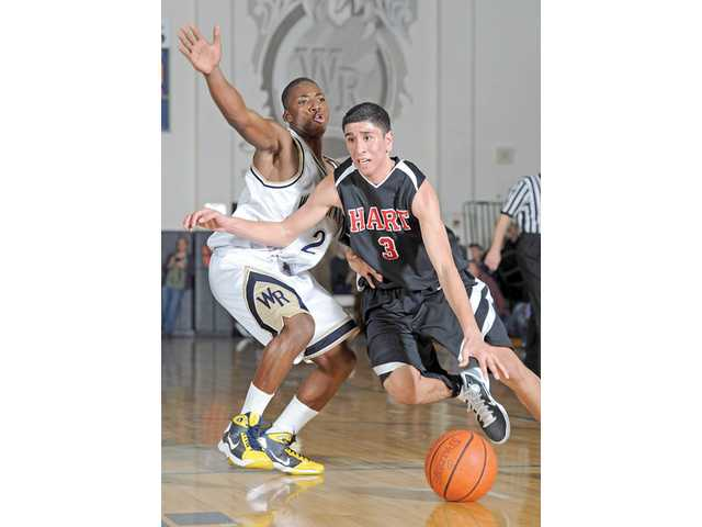 Hart guard Roman Delgado tries to dribble around West Ranch's Brian Polynice on Friday at West Ranch High.
