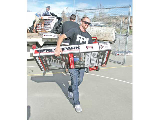 Freshpark Industries sales manager Matt Piercey helps unload cases of portable skate-park obstacles for assembly at the new 104-foot-by-55-foot skate park at the Castaic Sports Complex on Thursday.