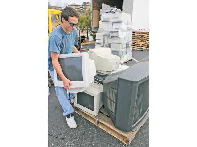 Jeremy Gordon, 18, loads a computer monitor onto a pallet with televisions and other electronics during the Canyon High School Advanced Placement environmental-science class holds a community electronic-waste collection drive in the Canyon High School parking lot in Canyon Country on Saturday.