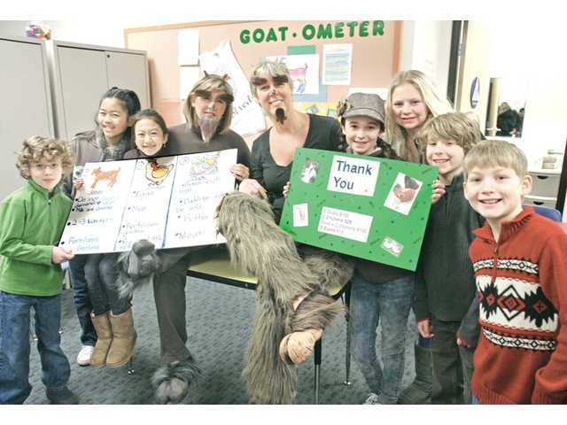 "The Santa Clarita Valley International Charter School home-study class, from left, Walter Sage, Emily Hyun, Tiffany Chang, school founder Amber Raskin, Home School Director Kathy Reyar, Fiona Perry, Tessa Delger, Dylan Perry and Daniel Larimer pose under the ""Goat-ometer"" with signs to thank the school's students for donations raised to purchase goats for impoverished families in other countries."