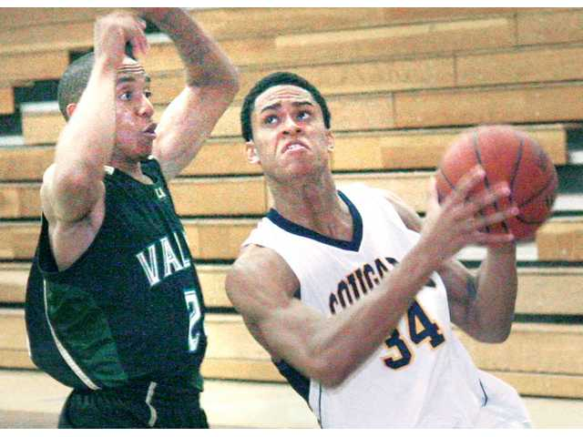 College of the Canyons' Wesley Bartole, right, looks to shoot against L.A. Valley's Alex Strauther on Saturday at COC.