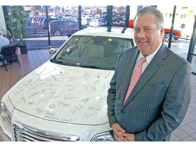 Dave Maxwell, general manager of California Superstores' Valencia Chrysler-Jeep-Dodge, poses next to a 2011 Chrysler 300 at his dealership on Monday. The car was autographed by stars at Sunday's Golden Globe Awards, and will make an appearance at a Vanity Fair event and the Academy Awards before being auctioned off for charity.