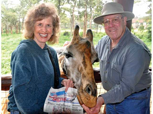 Joan Jacobson holds a copy of The Signal while her husband, Jeff, feeds Dixon the giraffe at the Giraffe Center in Nairobi, Kenya, in June 2010 during their East and South African vacation.
