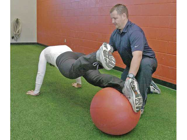 "Noland performs a stability ball plank exercise, another abdominal exercise recommend in ""The New Rules"", under Cosgrove's direction."
