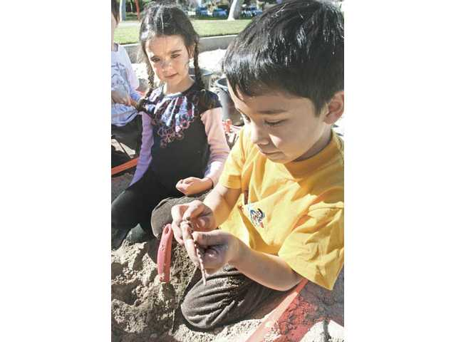 Charlie Schneider, 7, left, and Ricardo Diaz, 6, examine their findings during a simulated excavation at Valencia Glen Park in Valencia on Friday.