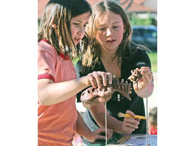 Belen Rivas, 9, left, Melanie Hyman, 9, mount the bones of a scaled-to-size model of Tyrannosaurus Rex that was buried during a Helping Hands Home School student exercise on archaeology