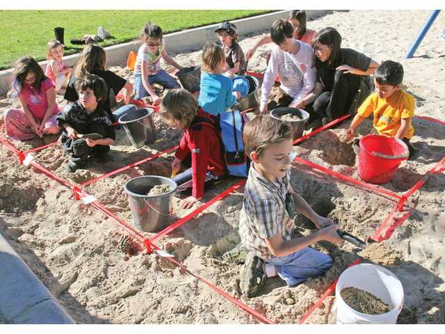 A group of more than 20 of the home-schooled children work at learning basic excavation techniques at Valencia Glen Park in Valencia.