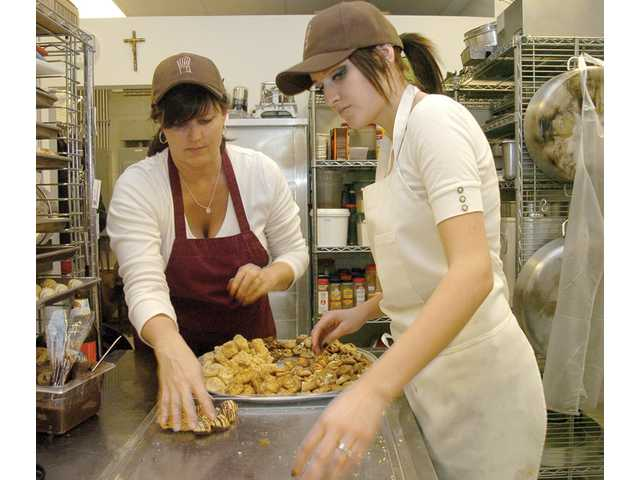 Mikayla Garrett and Laurie Rodgers work in the kitchen crafting desserts. The grand opening attracted former Playboy founder Hugh Hefner's girlfriend Kendra Wilkinson and her husband, Hank Baskett, of the Minnesota Vikings, to Rodgers' new storefront, which opened in December.