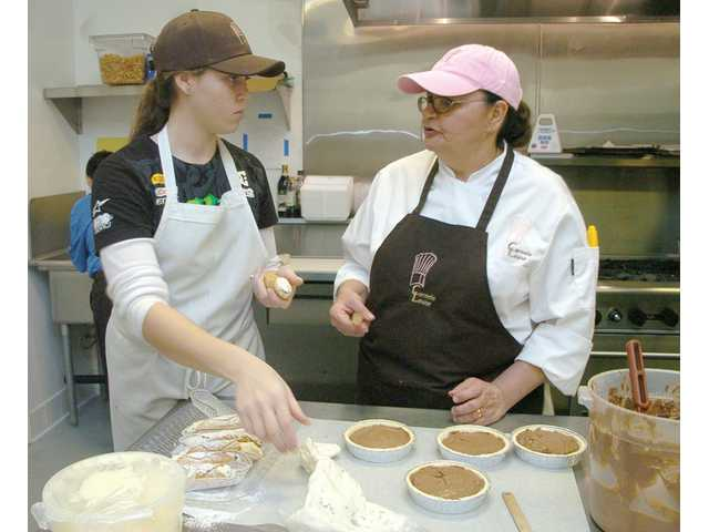 Molly Ann Bernstein, left, and Megan Kerns sort through baked goods to give away as samples at the recent grand opening of Carmela Louise Café in Saugus.