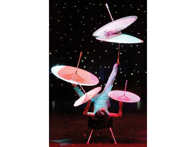 A performer from the Peking Acrobats balances umbrellas.