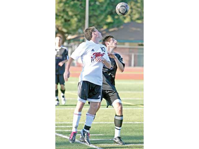 Hart's Ben Kret, left, goes for a header against Valencia's Aubrey Gierard on Tuesday at Hart High School.