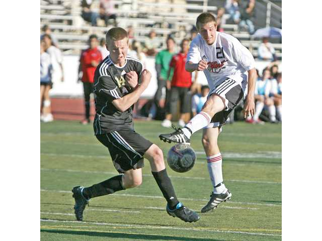 Hart's Bobby Phillips, right, tries to get the ball past Valencia's Chase Irwin on Tuesday at Hart High. The Indians won 2-1.