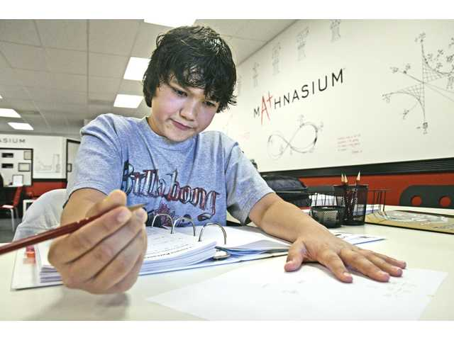 Mason Brown, 11,  works out his fractions on a piece of scratch paper.