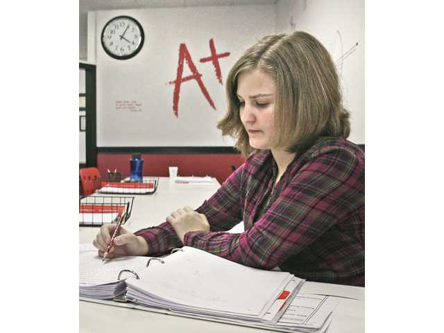 Mathematics cartoons decorate the walls that surround Emma Lee, 13, as she completes problems in her math workbook after school.