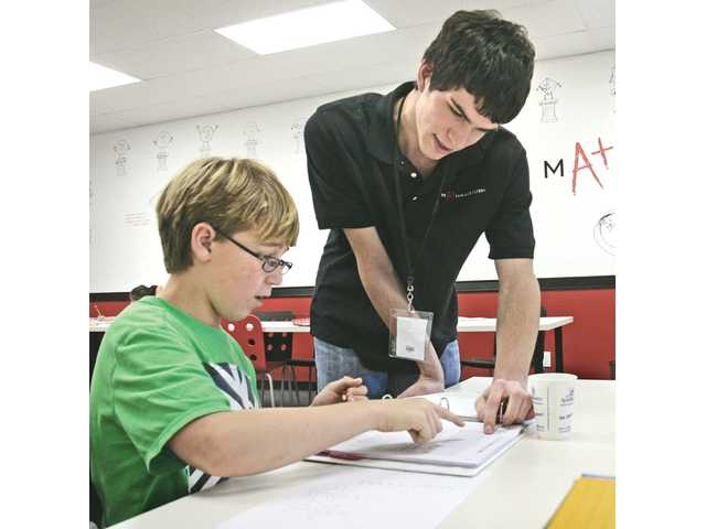 Math instructor Alex Lanza, right, works with Jacob Tollefson, 10, as he counts by groups of numbers at the Mathnasium office in Newhall. Mathnasium opened in September 2010, and has attracted students of all ages.