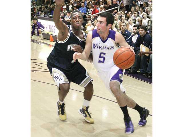 Valencia point guard Jake Kelfer (5) drives past West Ranch's Brian Polynice on Friday at Valencia High School. Polynice was one of five players ejected after a fight in the fourth quarter. The Vikings won the game 67-61.
