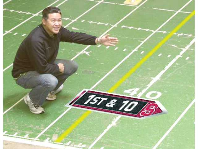 Valencia resident Ted Chen displays a first-and-10 arrow for a Stanford football game, which was taken from from a miniature one-eighth scaled-to-size football field at Sportsvision in Mountain View. Chen is the vice president of operations for Sportvision, the company which produces on-air graphics for all televised football games.