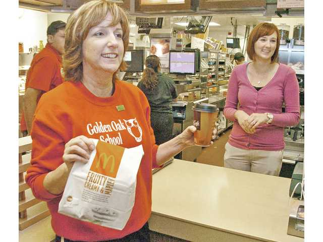 Fifth- and sixth-grade teacher Kim Tredick, left, calls out an order as sixth-grade teacher Amanda Jones helps behind the counter during Golden Oak Community School's McTeacher Night at the McDonald's on Golden Valley Road in Canyon Country on Thursday. Golden Oak teachers took orders and served students and families to raise money for equipment and student programs.