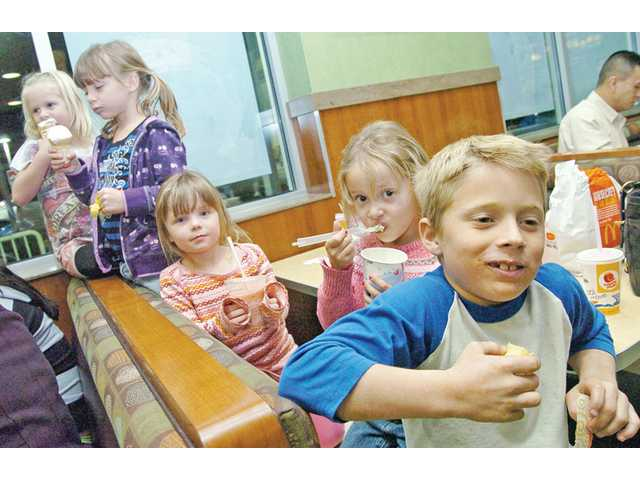 From left, Golden Oak kindergartners Mikayla Engbrecht, 5; Lauryn Traverso, 5; Emma Traverso, 5; and Grace Parker, 6, enjoy treats with third-grader Deryk Engbrecht, 8, during the fundraiser.