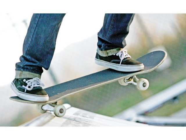 Skee Moschetti, 14, of Castaic, balances a truck of his skateboard on the top of a ramp in the new skate park at the Castaic Sports Complex on Tuesday.