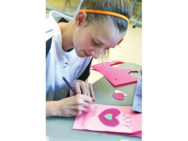 Katherine McKenna, 13, of the Valencia Heat soccer team makes a Valentine's Day card for a member of the Navy at the Hearts For Heroes at the Newhall Community Center on Saturday.