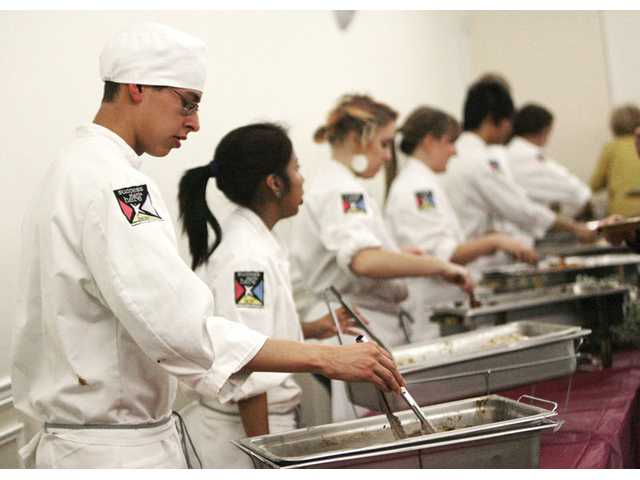 Canyon High School student Ruben Olmedo, 17, left, joins other students in William S. Hart Union High School District's Regional Occupational Program advanced culinary class in serving food to guests at the Golden Apple Awards dinner at the Santa Clarita Sports Complex Activities Center on Monday.
