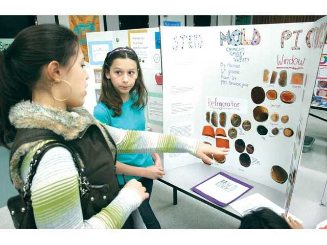 Sixth-grader Hannah Horowitz, right, discusses her experiments on growing mold in different environments with judge Carissa White at the science fair.