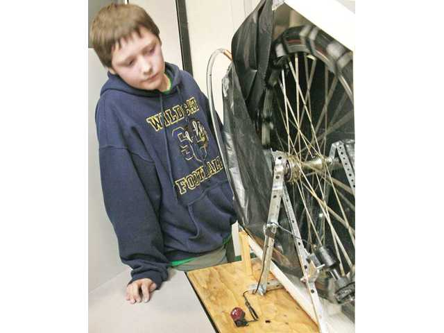 Sixth-grader Riley Rathstone demonstrates his team's homemade water-powered hydroelectric generator as he participates in the Meadows Elementary School science fair in Valencia on Thursday.