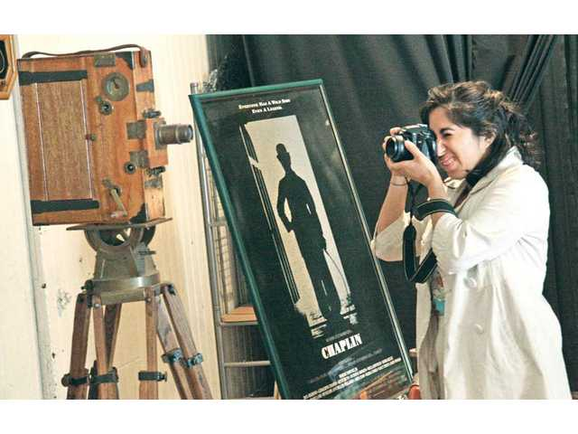 "The Master's College student Alicia Ramos takes a photograph of a vintage movie that was used as a prop in the 1992 film ""Chaplin,"" starring Robert Downey Jr.  The camera was on display as part of the Santa Clarita Valley 2011 Chaplin Fest held at William S. Hart Park in Newhall on Saturday."