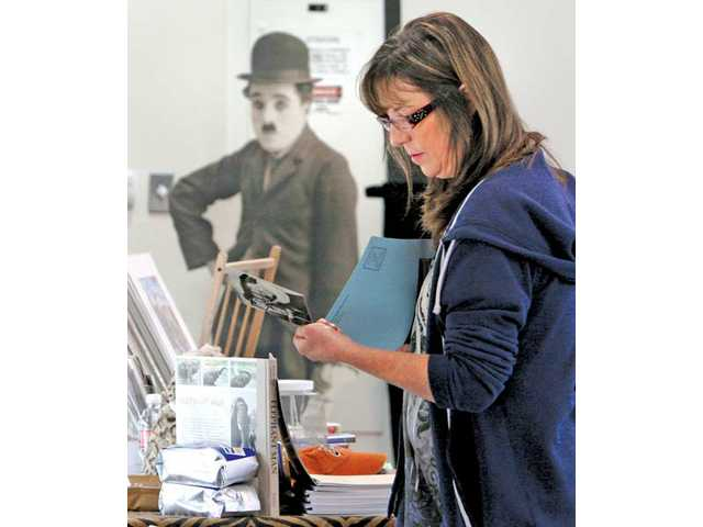 "Film enthusiast Linda Casebolt, of Newhall, looks through Chaplin photos for sales as a cut-out figure of Charlie Chaplin as ""the little tramp"" looks on at the 2011 Santa Clarita Valley Chaplin Fest held at William S. Hart Park on Saturday in Newhall."